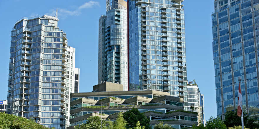 A shot of modern architecture, with a Canadian flag to the side, in sunny Vancouver.
