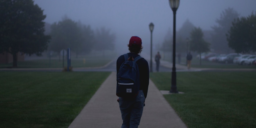 A lone student stands with his back to the camera, looking out across the foggy campus of Briercrest College.