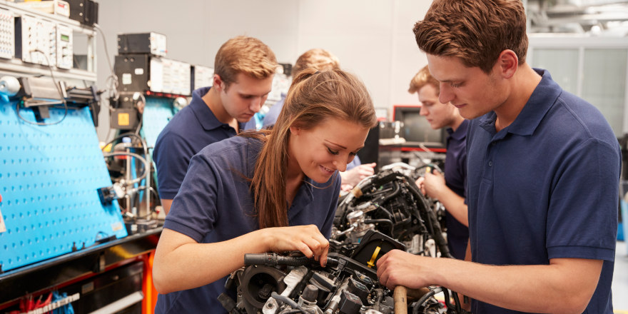 Students happily work on an engine in class.