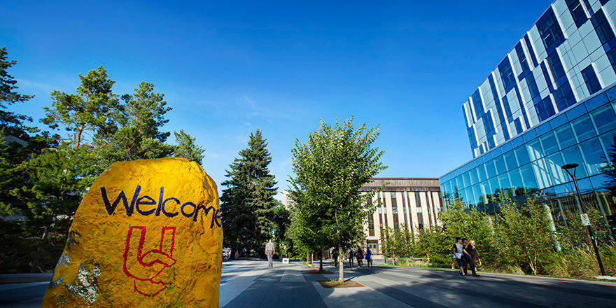 A sunny exterior of the University of Calgary campus, with a painted rock in the foreground.
