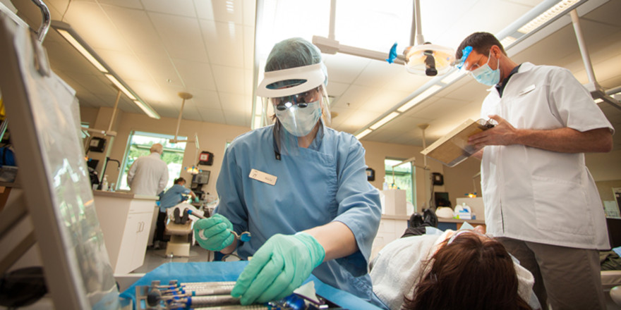 A dental hygienist tends to a patient under the eye of her supervisor.