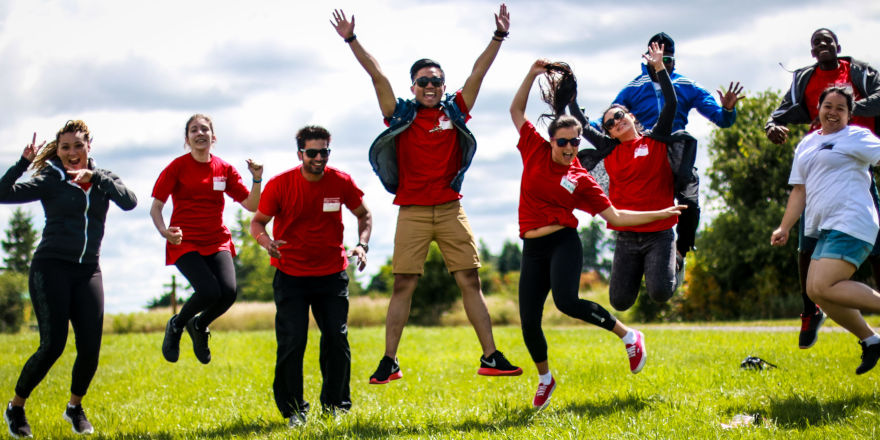 A group of excited students jumps for joy at George Brown College.