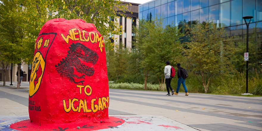 A bright red rock emblazoned with a welcome to the University of Calgary campus.