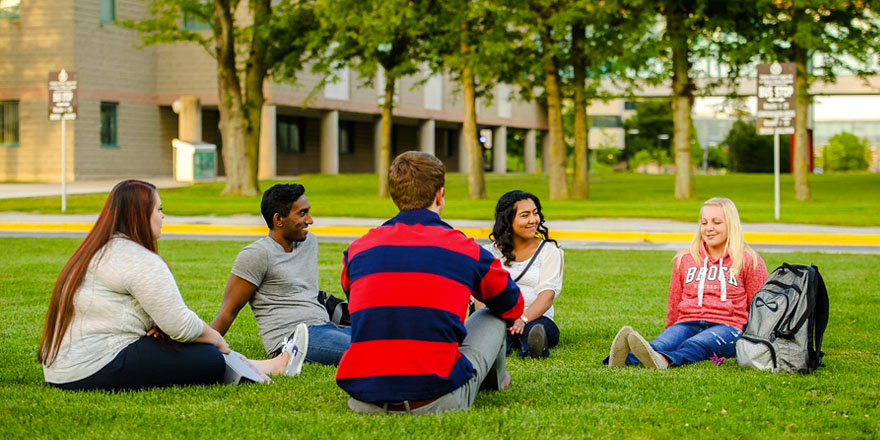 Students enjoy the green grasses of Brock University, as part of a balanced day of school, work, and extracurricular activities.