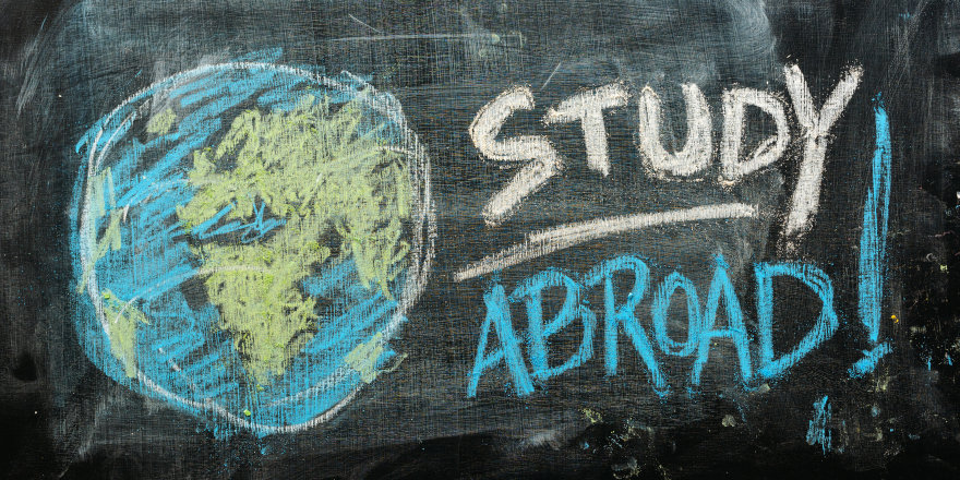 A chalk drawing of the globe on a blackboard, with the words 'Study Abroad!' written alongside.
