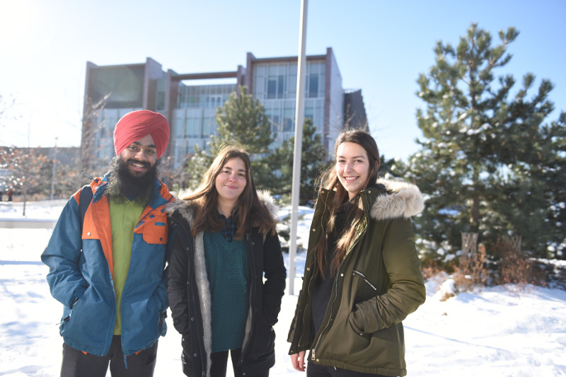 A group of international students smiles outside Centennial College on a beautiful winter day.