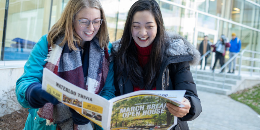 Two University of Waterloo students cheerfully explore the UWaterloo newspaper, discussing how to finalize their university shortlists and deciding on where to apply.