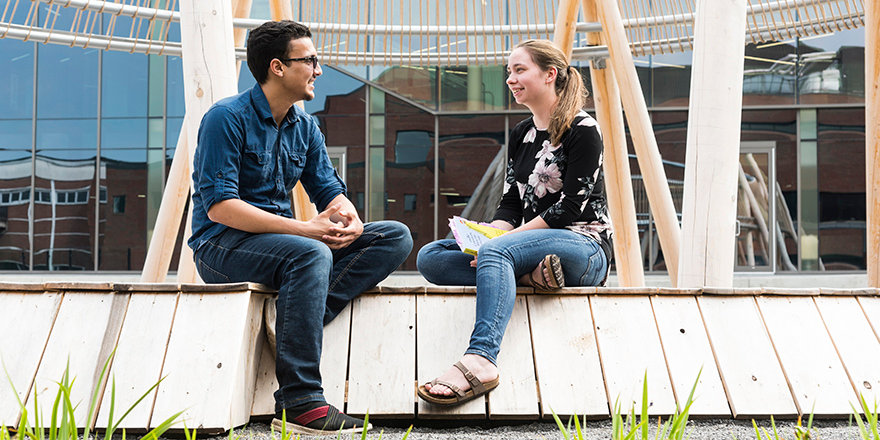 Algonquin College students sit outdoors discussing their best strategies for keeping their mental health and wellbeing strong during the semester.
