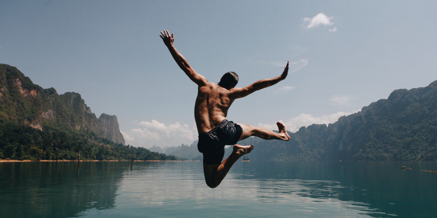 A student with a sudden day off leaps joyfully into a lake.