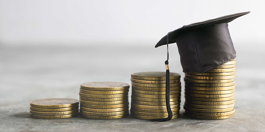 A stack of coins with a tiny mortarboard symbolizing the financial benefits of studying abroad for Canadian students.
