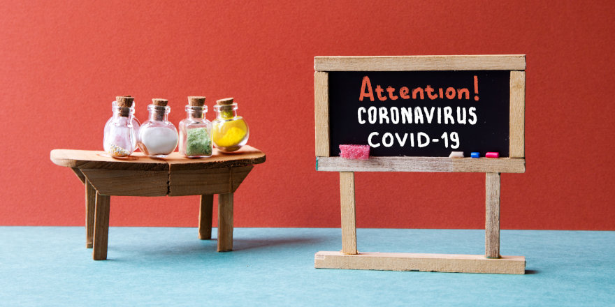 A colourful laboratory with a chalkboard reading Attention! Coronavirus COVID-19.