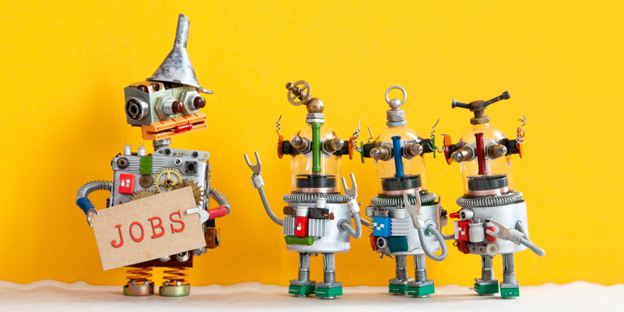 Three little robots line up with a larger robot holding a 'Jobs' sign. Each of the wee bots is excited to be employed!