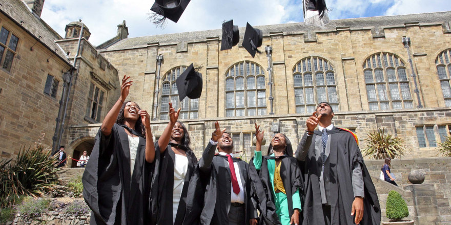 Proud graduates of Bangor University throw their mortar boards into the air in celebration.