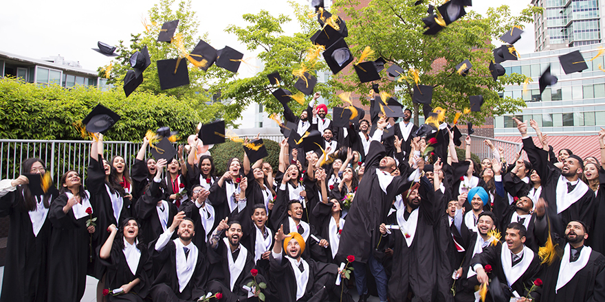 Graduates of Alexander College throw their mortar boards into the air, having achieved a university degree thanks to a transfer program with the college.